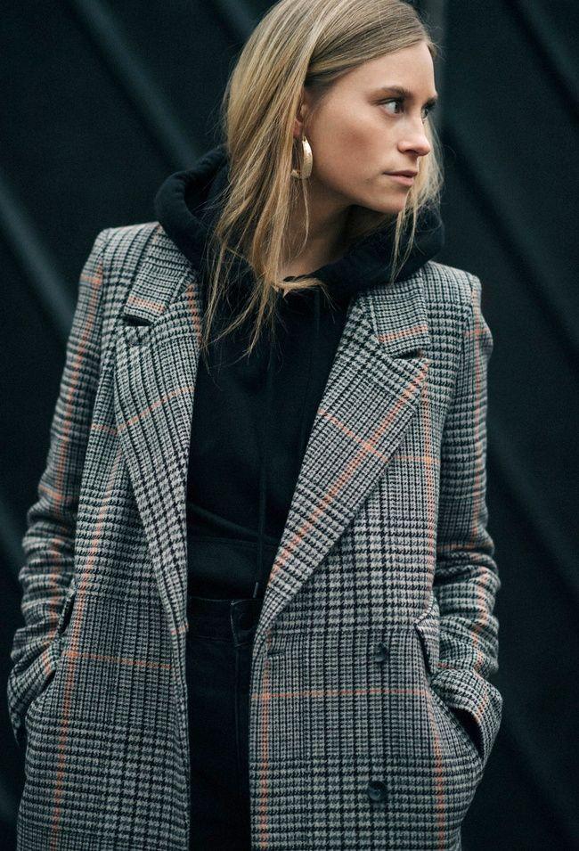 Le manteau à carreaux se marie bien à la nonchalance sporty du sweat à capuche (photo The Fashioneaters)