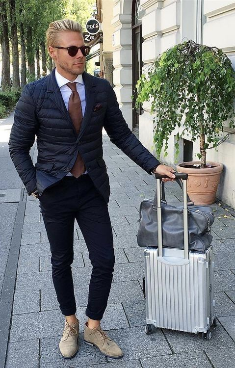 9d10fd9a4b8 Dapper combo inspiration with a navy quilted jacket white spread collar  shirt brown silk tie navy denim tan shoes gray leather duffle bag  sunglasses. model ...