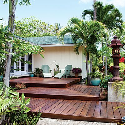 Instead of stairs, a three-level deck steps up to the front door of this raised post-and-pier-house on the island of Oahu.    Tropical accessories on the deck and throughout the garden turned this entry into a personal paradise