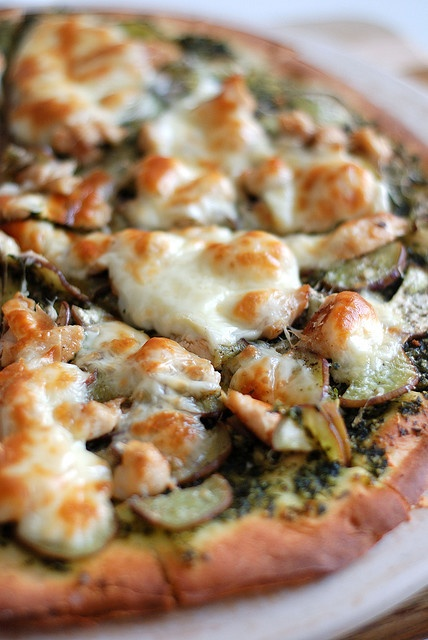 Grilled chicken pesto pizza with Greek olives, tomato basil feta, sun dried tomatoes.