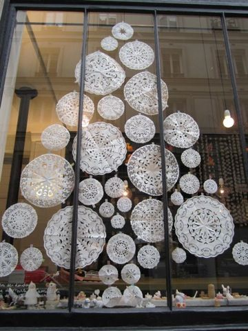 A paper doily Christmas window design.. cute! They look like snowflakes. DIY