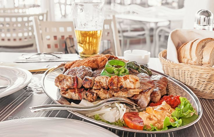 meat beef pork chicken and Turkey with grilled vegetables on a large platter with fries, peppers, tomatoes, eggplant, grilled