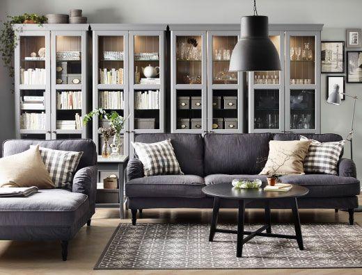 Vardagsrum med grå 3-sits soffa, schäslong och runt svart soffbord. Här med fyra grå vitrinskåp.
