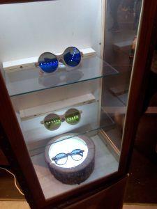 gafas de madera en vitrina de cristal