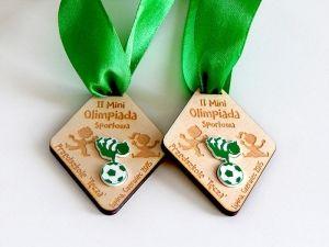 Pamiątkowe medale sportowe dla dzielnych dzieci uczestniczących w ll  Mini Olimpiadzie. Medale o nietypowym kształcie, ze sklejki i zielono-białego laminatu grawerskiego.