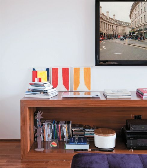 Revestido de mogno, o aparador baixo (2,80 x 60 cm, altura de 40 cm) pertencia ao antigo morador e foi vendido com o apartamento. O móvel segue a linha clean, privilegiada pelos novos proprietários. Telas coloridas da Arterix.