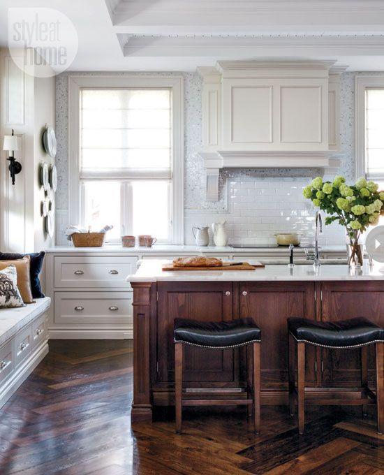 herringbone wood floors + wood kitchen island + white kitchen cabinets + marble countertop