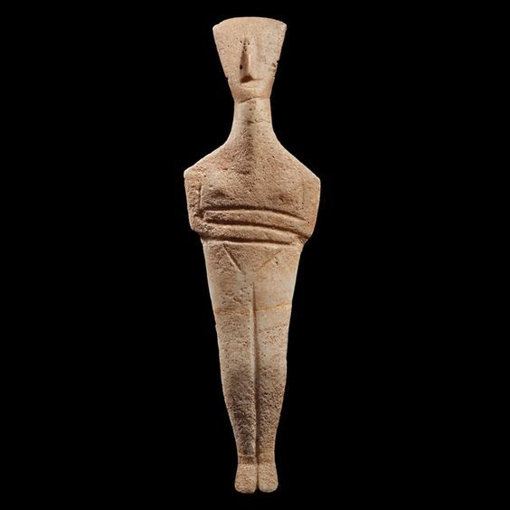 Cycladic marble figurine of the Dokathismata type,  second half of the 3rd millennium B.C. 2400-2100 B.C. Dokathismata type, compared to the statuettes of the Spedos type, the most common and renowned version, characterized by fi nely modeled and somewhat rounded shapes, have a definitely more slender silhouette, sometimes angular, but whose general appearance conveys an impression of formal elegance, 21 cm high. Private collection