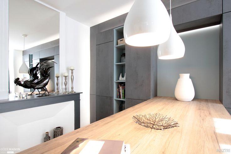 Les suspensions déco de cette cuisine blanche éclairent tout en douceur la table à manger conviviale