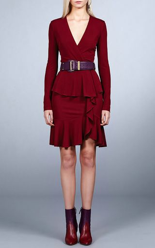 This long sleeve **Roberto Cavalli** dress features a sheath silhouette with a crossover v-neckline, a peplum waist, and a ruffled trim along the skirt.