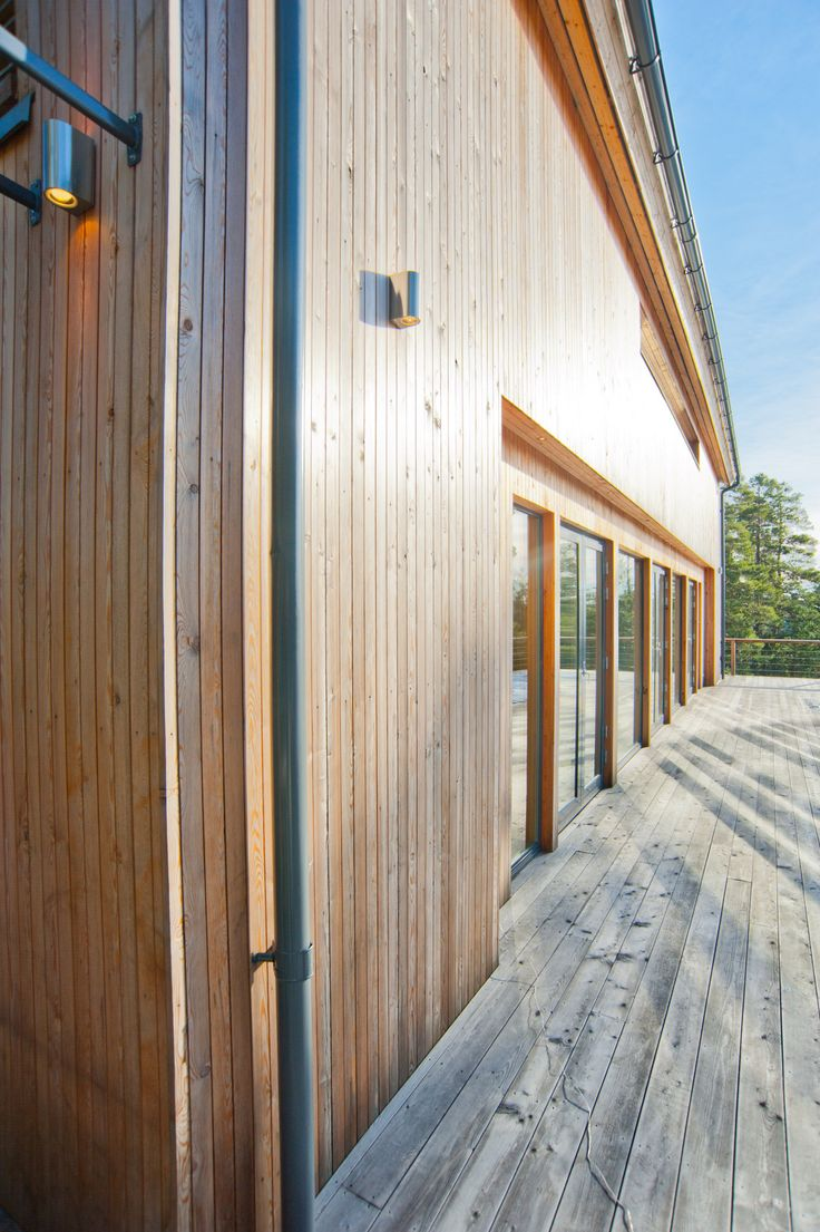 Modern log house, larch facade and terrace.
