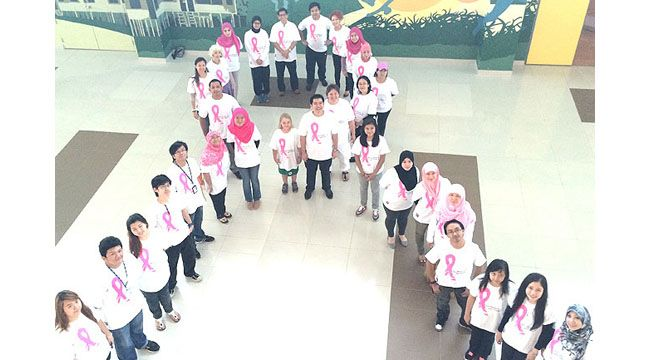 Participants forming a human ribbon at the launching of the Breast Cancer Awareness Month