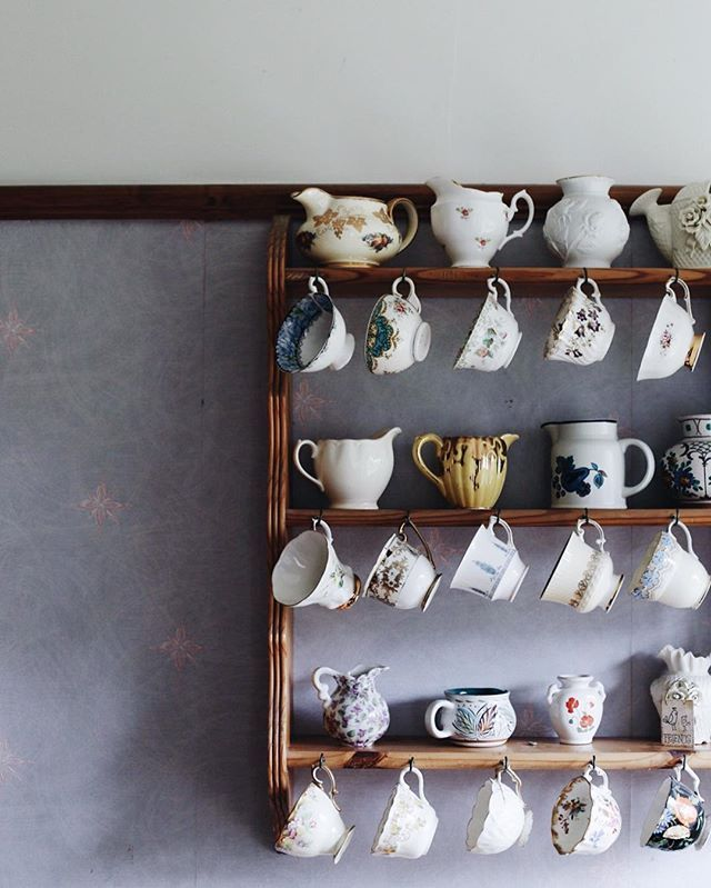 Charming kitchen display of teacups, creamers and pitchers.