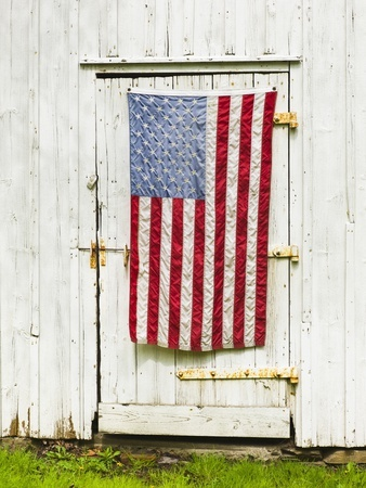 American flag draped on the door of a barn.