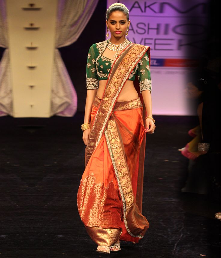 A beautiful draped ghagra in rust coloured silk with a dull green net dupatta draped over it. | Neeta Lulla Online Store