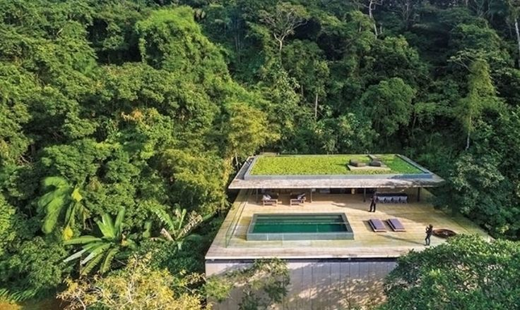 Casa Guaruja features orthogonal forms dominated by large overhangs, and plenty of outdoor spaces overlooking a thick pine forest.