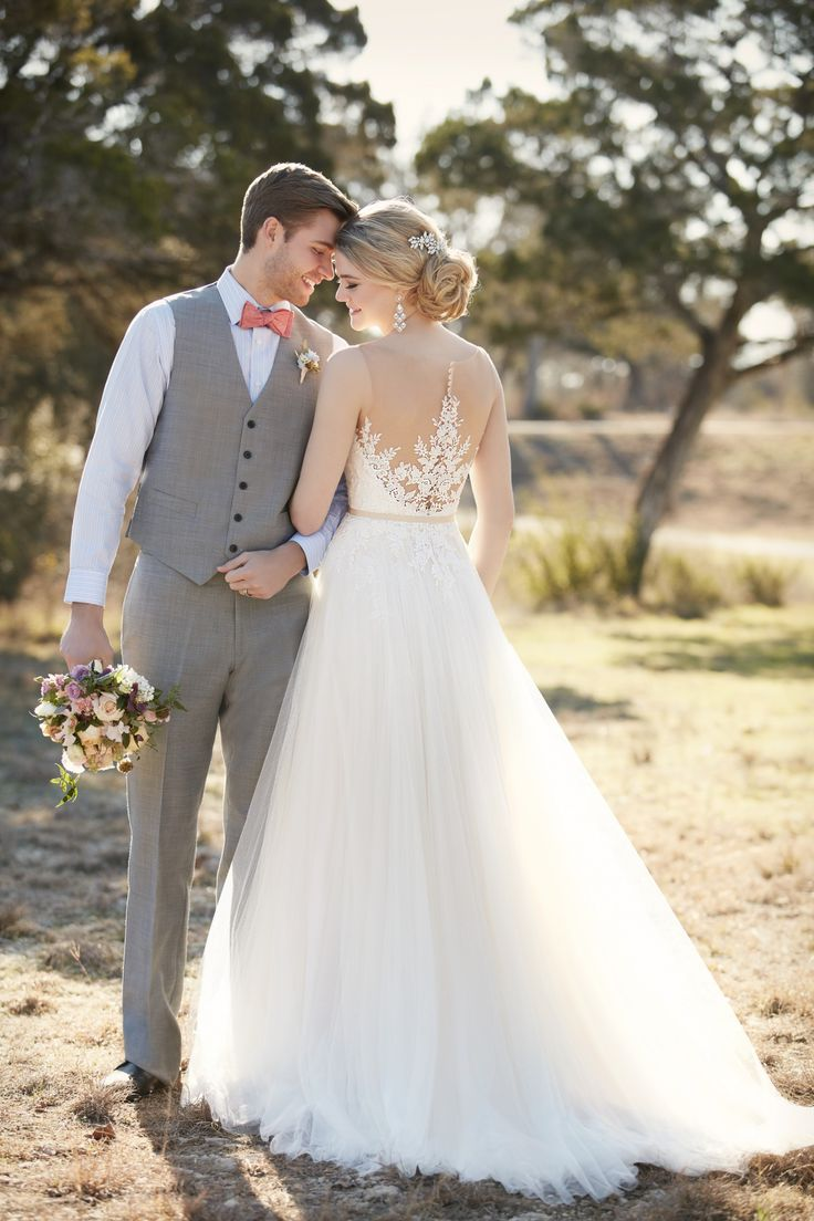 This A-line wedding dress from Essense of Australia features an illusion lace bodice with glistening Diamante accents. The French tulle skirt falls gracefully to the floor into a romantic court train. The back zips up with ease under sparkling crystal buttons. Accent your waist with a 1/2' beaded grosgrain belt.' (sp)