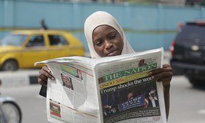 A muslim woman reads a newspaper on a street in Lagos, Nigeria.