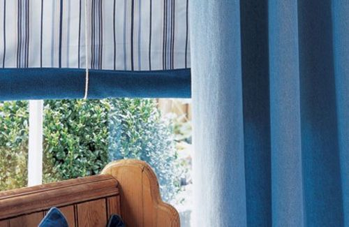 Unlike classic roller blinds, this type of roller blind rolls from the bottom of the blind upwards, the roll being created by lengths of cord - as seen here. Ideal for a living room that's relaxed in style, these blinds are more fiddly but more decorative than plain rollers.