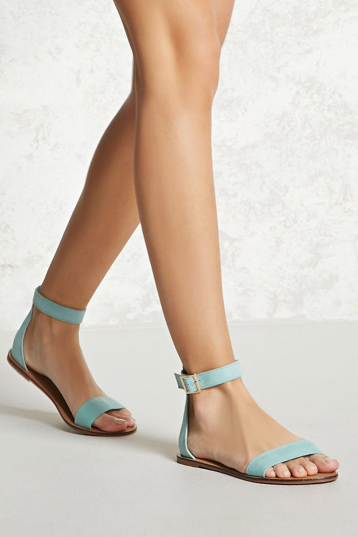 A pair of faux suede sandals featuring an ankle strap with a high-polish belt buckle, an open toe, and a slight heel.