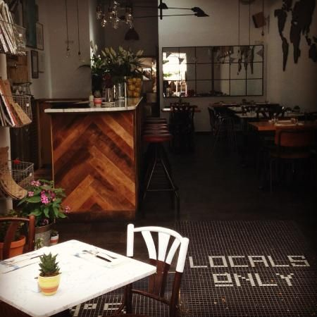 Locals Only IBIZA  Reclaimed Chevron Wood Bar, Penny Tile on the Floor Entrance, Dipped Wood Chair, Planters, Marble Table.