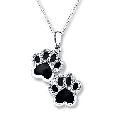 Petite paw prints in onyx and sterling silver with diamond accents trail from an 18-inch box chain in this playful pendant for her. The necklace fastens with a lobster clasp and has a total diamond weight of 1/10 carat. Diamond Total Carat Weight may range from .085 - .11 carats. Black Onyx is subject to a dye treatment which may not be permanent. Gently clean by rinsing in warm water and drying with a soft cloth.