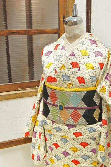 端正な青海波文様の所々に、山吹色や藤紫、紅色の本絞りで優しく色付けされた正絹綸子の付下げ小紋です。