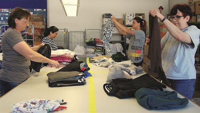 Mitarbeiter beim Sortieren von Textilien-Spenden – 4.000 Tonnen sind es pro…