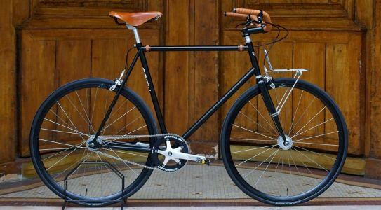 Black Porteur bike style with brown handlebars and saddle. See more stylish women on bikes at melisinestudio.com and @melisinestudio on instagram.