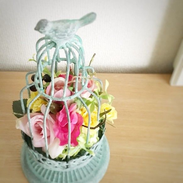 アンティーク調のグリーンの鳥かごに、上質なアンティフィシャルフラワーをアレンジ。ピンクのローズやスイトピーなど、キュートなアレンジに仕上げました。アーティフィシャルフラワーだから、水やり不要でお手入れも簡単。母の日や引越し祝いなど、大切な方へのギフトに♪◾︎サイズ:直径 約13cm × 高さ 約25cm◼︎お花はアーティフィシャルフラワー(造花)です。◼︎セロファンでラッピングしてお届け致します。クリアケースラッピングをご希望の場合は、有料ラッピング(500円)を選択して下さい。◼︎ご希望の方にはメッセージカードを無料でお付けいたします。◼︎写真はできるだけ実物の色に近いものを掲載するよう努めておりますが、お使いのPCやスマホ環境等によりイメージが異なる場合がございますことをご了承下さい。◼︎他のECサイトでも販売しているため、入れ違いで在庫がなくなった場合は、ご購入いただくことができない可能性がございますことをご了承下さい。