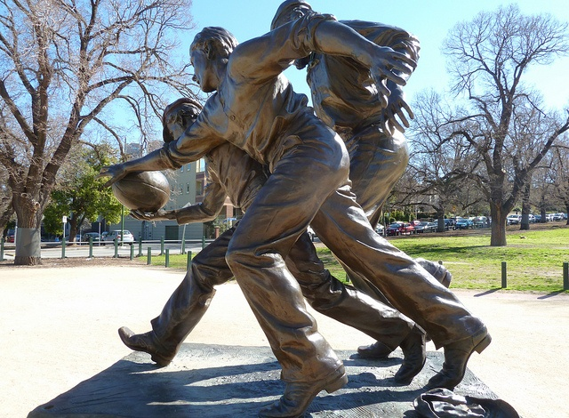 Australian Rules Football the beginning. Sculpture by Louis Laumen 2001. The first recorded game of Aussie Rules Footy began on the tree-dotted parklands outside the Melbourne Cricket Ground by teams from Scotch College and Melbourne Grammar School on 7 August 1858. The Australian Rules Grand Final is held at the 'G' known world-wide as the Melbourne Cricket Ground or M.C.G.