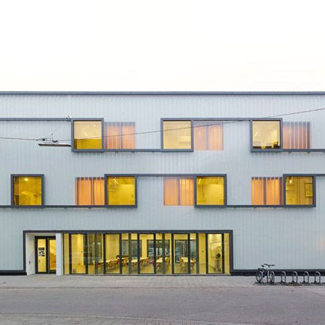 A glass wall spotted with reflective yellow and orange windows creates a false facade for this extension to a secondary school in south-west Germany