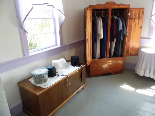 Inside an Amish House, in a bedroom.  Headcoverings on top of quilt chest. ~ Amish Home Inside ~ Sarah's Country Kitchen ~