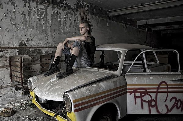 A punk sitting on top of old East german car, Trabant.