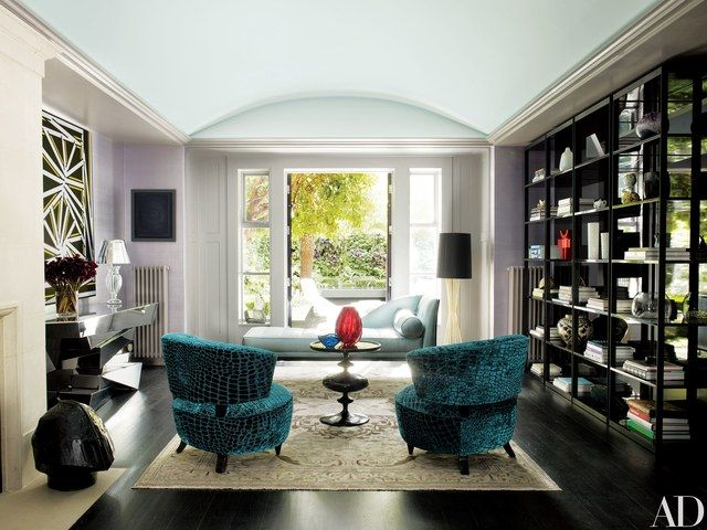 In the living room, Christian Liaigre bookcases face Gilbert Rohde slipper chairs from Todd Merrill Antiques, a Tommi Parzinger daybed from Palumbo, and a De La Espada floor lamp. A Nicholas Krushenick painting hangs above an Hervé Van der Straeten console from Ralph Pucci International, which displays a lamp designed by Philippe Starck for Flos; the silk-on-paper wall covering is by Stark, and the rug is by ABC Carpet & Home.   archdigest.com