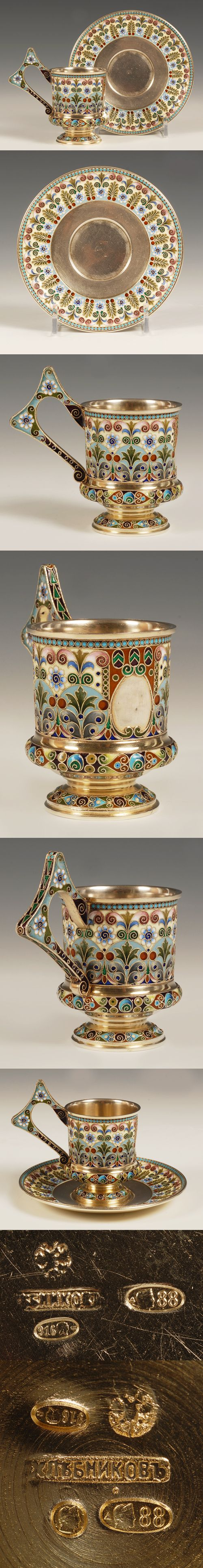 A Russian silver gilt and shaded cloisonne enamel demi-tasse cup nd saucer, Ivan Khlebnikov, Moscow, circa 1908-1917. The footed cup enameled throughout with multi-color flower-heads and foliate designs on cream and blu grounds, the saucer similarly decorated around the rim.
