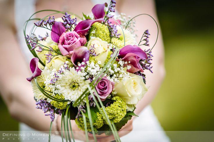 Bruidsboeket in kleurrijke paarsrode en crèmekleurige tinten met paars-rode calla bloemen, paars-rode en crème rozen en gipskruid.