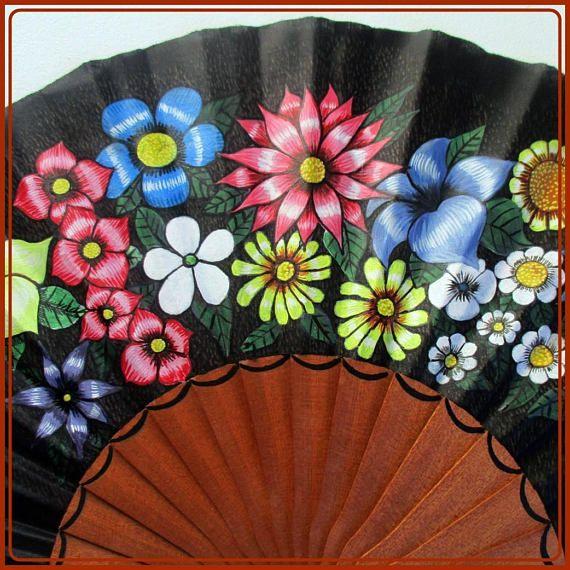 Abanico artesanal español, de madera de sipo, madera de gran calidad, pintado totalmente a mano. Es un modelo único y exclusivo. Abanico de color negro, con motivo de flores. Excelente y original abanico para regalarte o regalar. Medidas: (ancho x alto) Abierto:48,5cm x 24,00cm