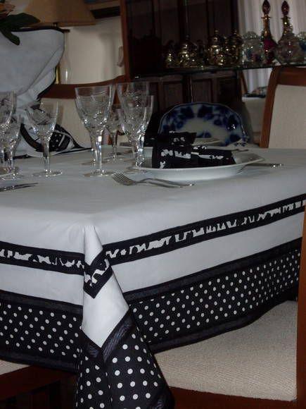 Toalha de mesa confeccionada em tecido de algodão branco, com barrado preto com bolinhas brancas e estampado em branco e preto, nas dimensões 1.50mx1.50m. Os guardanapos e os porta-guardanapos são vendidos separadamente.