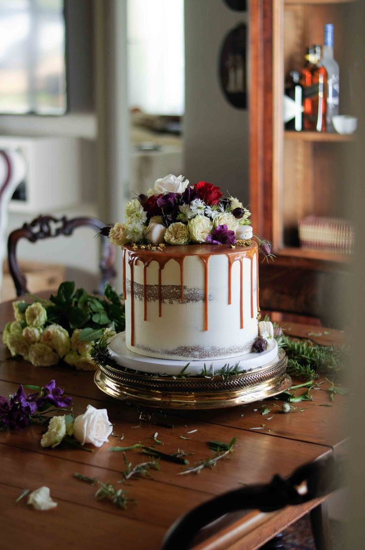 Semi-naked buttercream cake with caramel drip and fresh floral by LionHeart