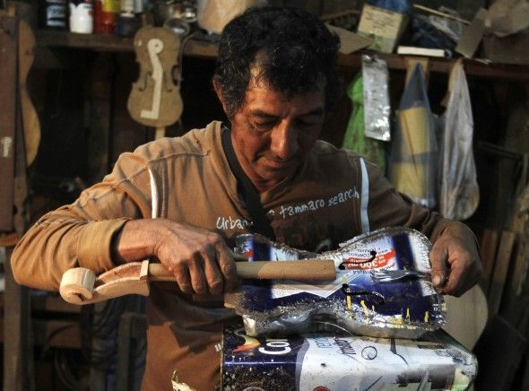 Trash recycler and craftsman Nicolas Gomez makes a violin from a paint tin and dinner fork for the Orchestra of Recycled Instruments of Cate...