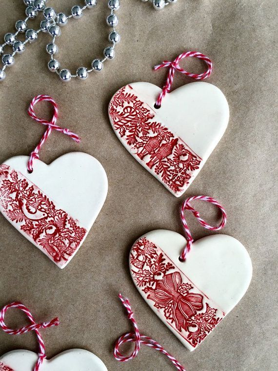 A set of three white ceramic heart Christmas ornaments that can be used as Christmas tree decoration or gift tags.  The heart is made of white earthenware clay and fired twice around 1000°C. First the impression on the heart was inlaid with red underglaze and then the ornament was coated with transparent glaze. The backside where the ornament was touching the kiln was left unglazed. The ornaments come with the red and white ribbon  Size: 6.5cm // 2.6