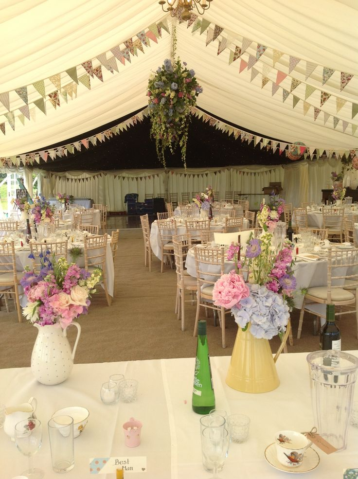 Summer flowers in pretty jugs look the part in this country wedding marquee