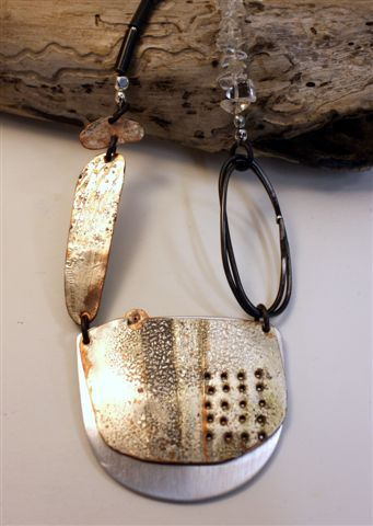 Noela Mills wabi sabi jewellery. Recycled heat treated metals, steel wire, aluminium, clear glass beads.