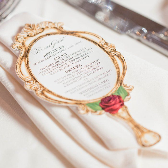 "The dinner menu was in the shape of the hand-held mirror from Beauty and the Beast, with ""Be Our Guest"" written across the top."