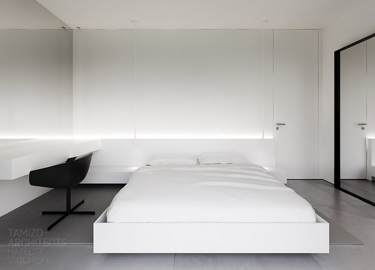 The bedroom is kept absolutely simplistic. A white platform bed has a softly illuminated headboard that runs directly to a bedside desk that doubles as a dressing table. A mirror at each side of the room makes the space feel triple its actual width.