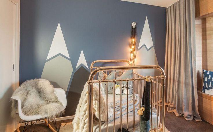 dessin montagne géometrique en couleurs claires sur un fond bleu ardoise dans la chambre bébé