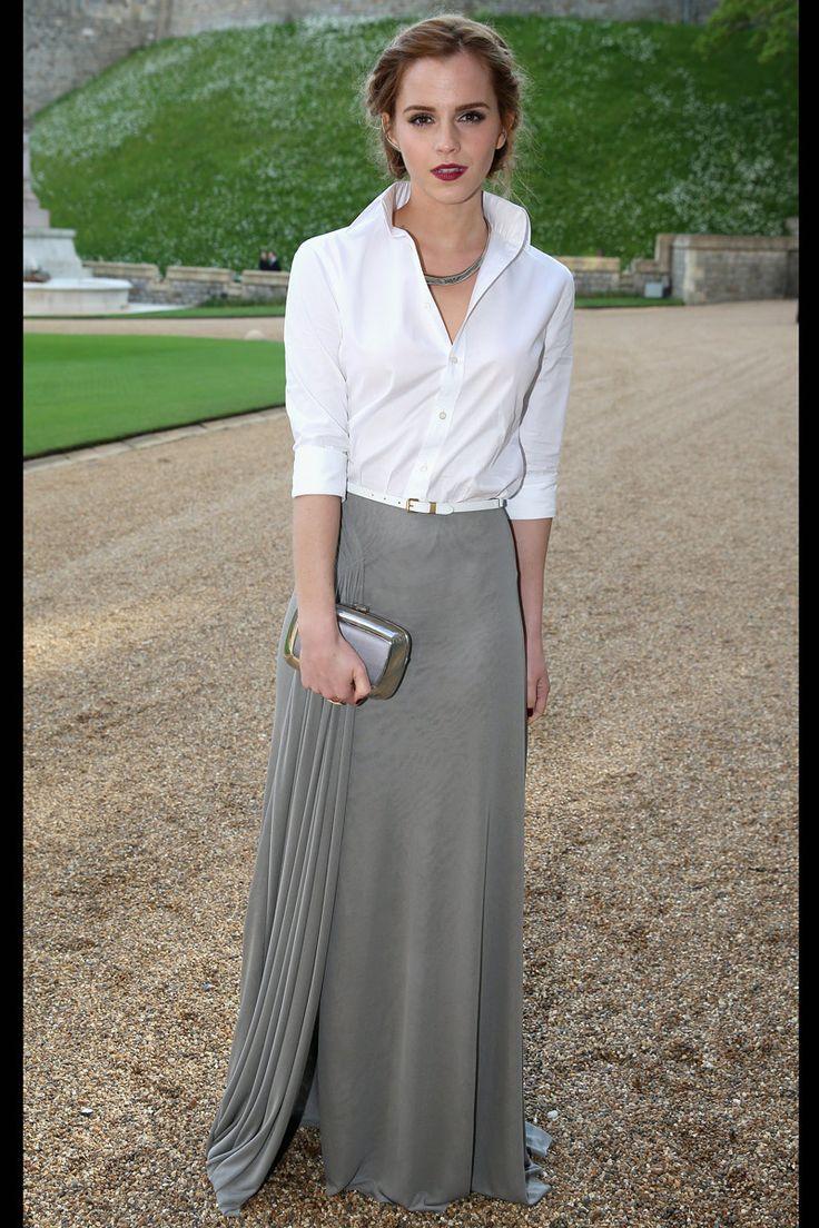 Emma Watson con camisa blanca y falda gris larga en un evento de tarde.