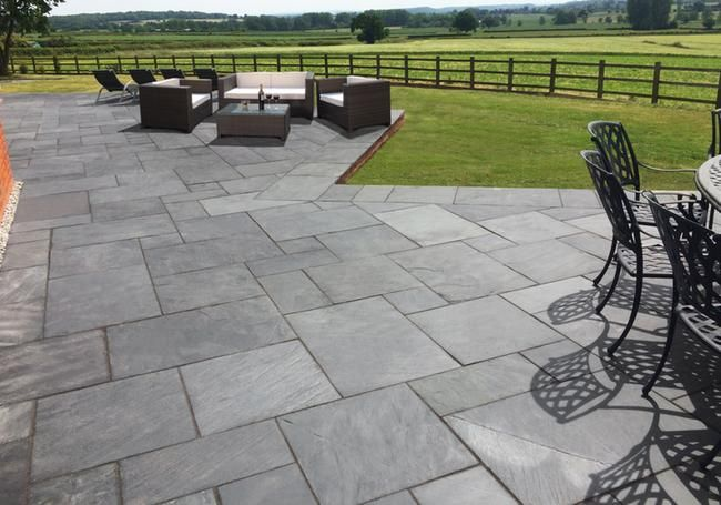 This beautiful natural slate paving is a stunning, dark, hard wearing slab with a slightly riven surface giving it texture and interest. Looks amazing in this large patio area.  #grey #slate #paving
