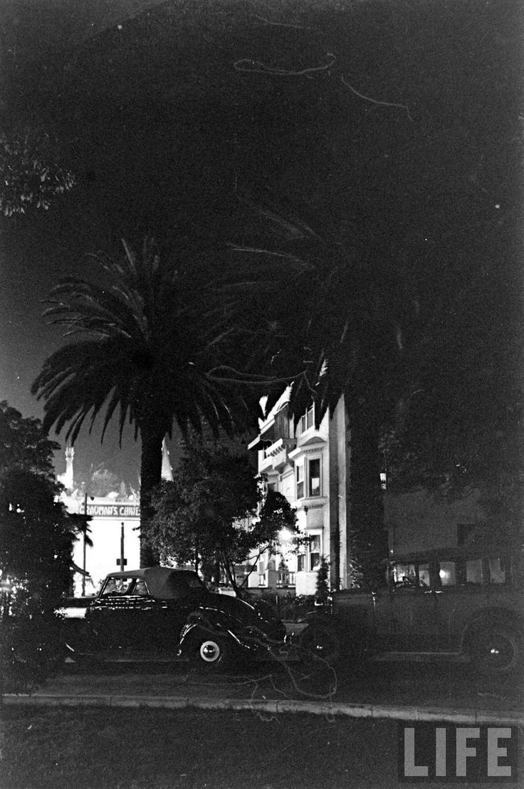 """Here's an atmospheric night shot from circa 1936! Through the foliage out front of the Hollywood Hotel we can see the bright lights of the neighboring Grauman's Chinese Theatre. It makes me wonder what was playing at the time: """"A Tale of Two Cities"""" or """"Modern Times"""" or one of my favorite films from that year, """"Wife Versus Secretary"""" starring Gable, Loy, and Harlow."""
